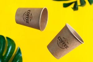 在黄色背景上的浮动生态友好纸一次性样机杯与绿色的棕榈叶